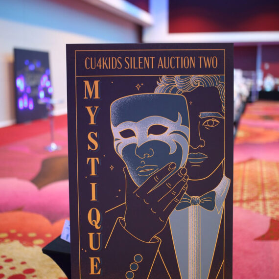 """A photo from the event showing a man holding a vintage mask design in front of his face to play off the """"Mystique"""" theme of this other silent auction"""