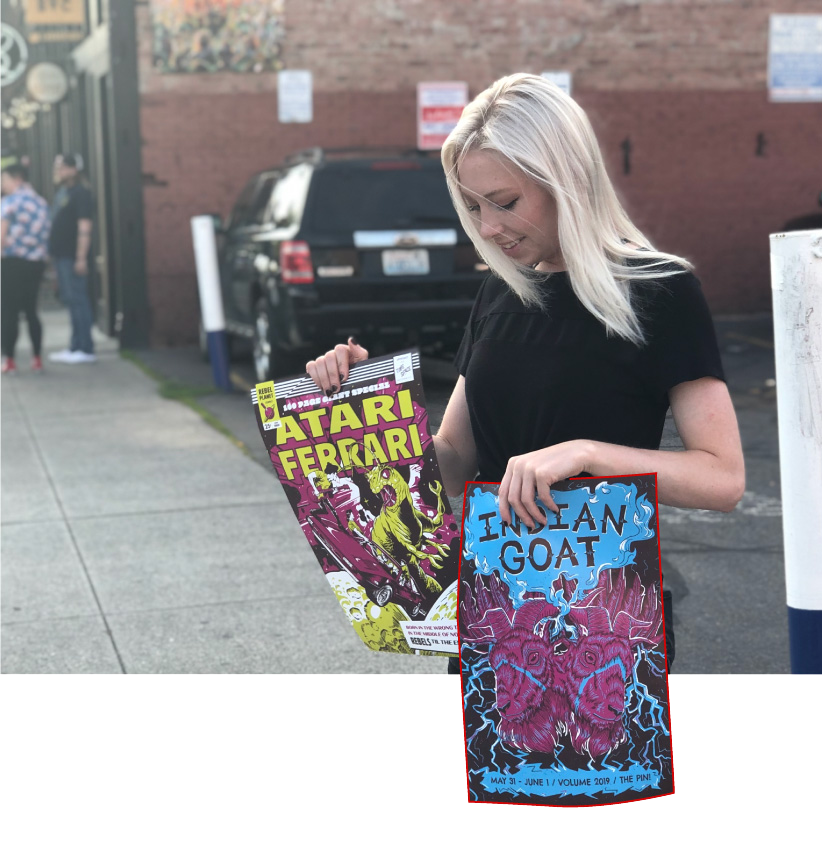 Photo of Kelsea holding band posters to benefit Songs for Kids Foundation. Posters by Kelsea Rothaus and Jon Merrell.